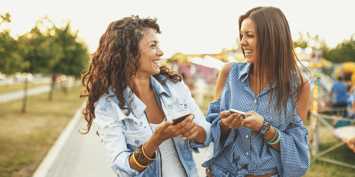 two ladies walking a carnival laughing while holding smartphones