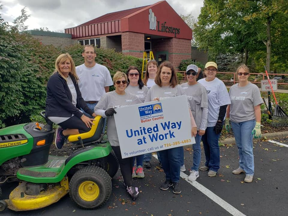 NexTier Bank employees helping clean up outside Lifesteps in Butler, PA holding a United Way at Work sign