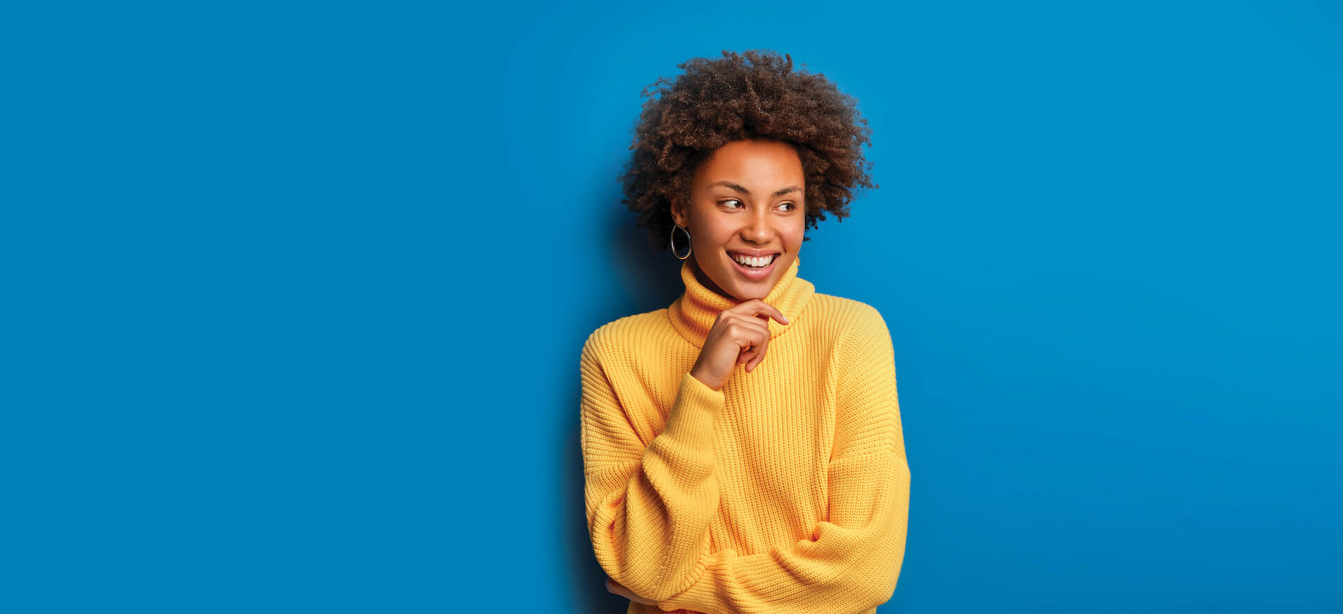 Woman standing infront of blue background in yellow sweater smiling