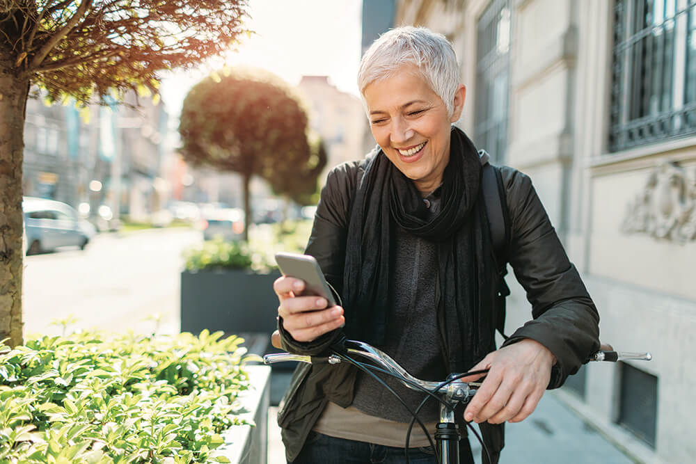 woman with bicycle stopped looking at smartphone smiling
