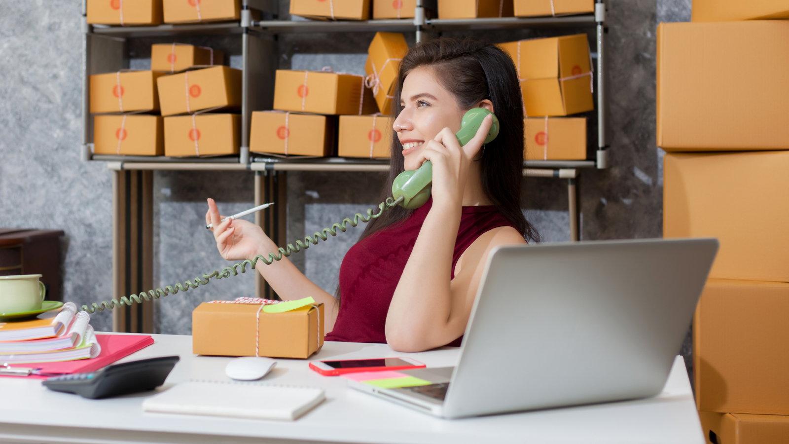 business woman on phone with shipping box and computer on desk