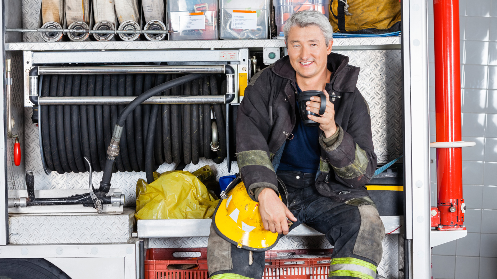Firefighter relaxing on firetruck while drinking coffee