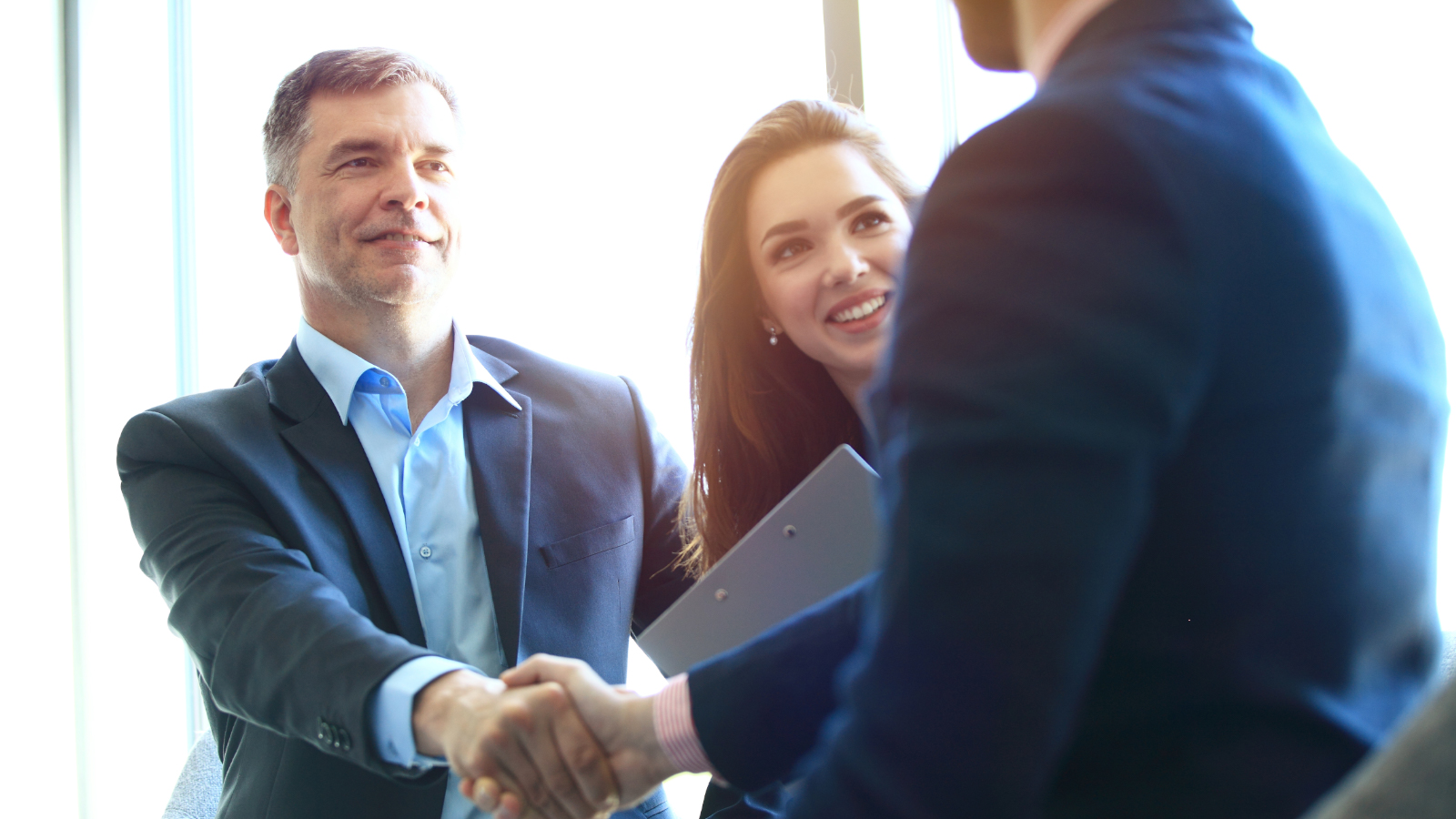 business man and woman shake hands with client