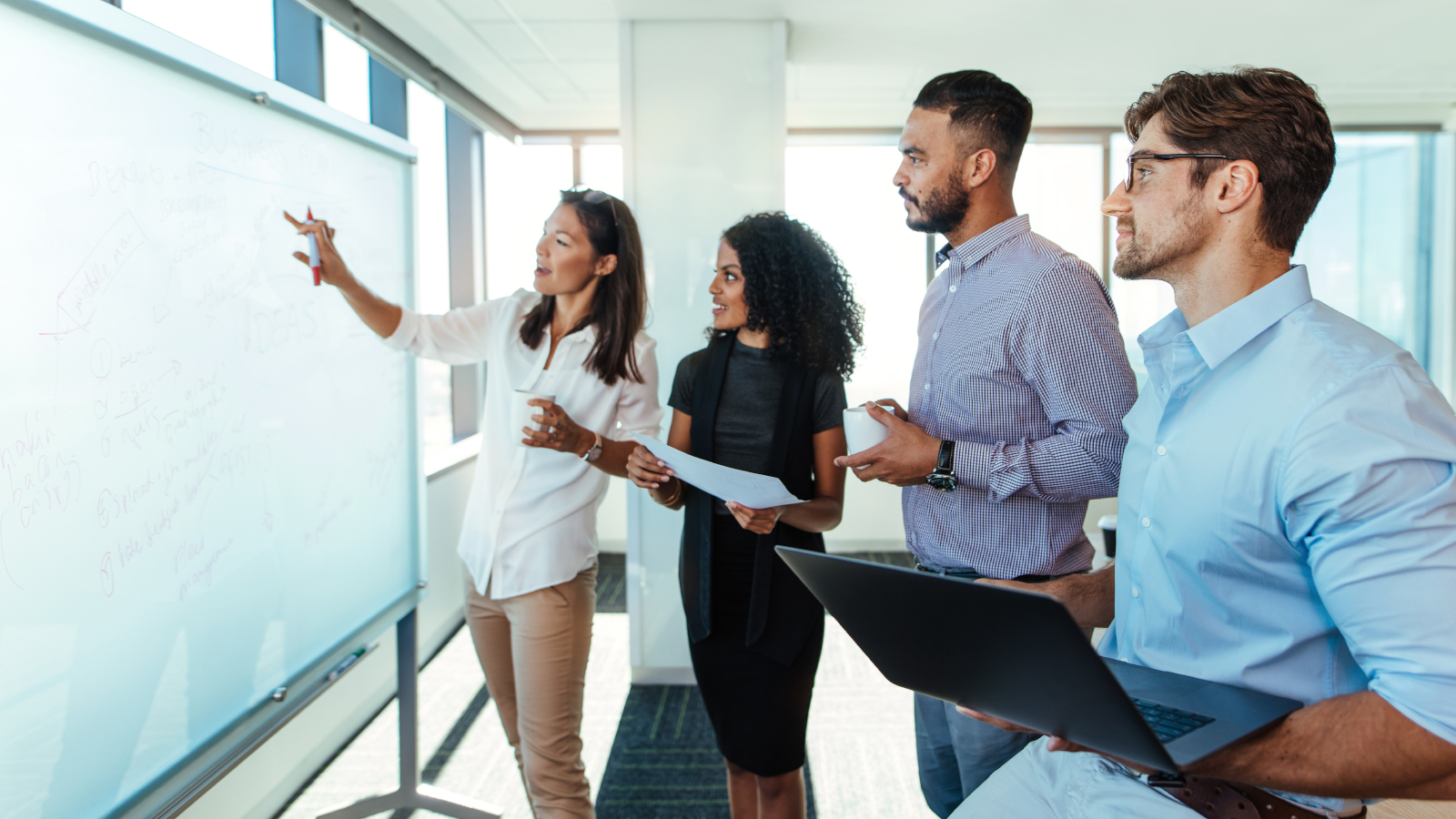 business team reviewing plan on white board