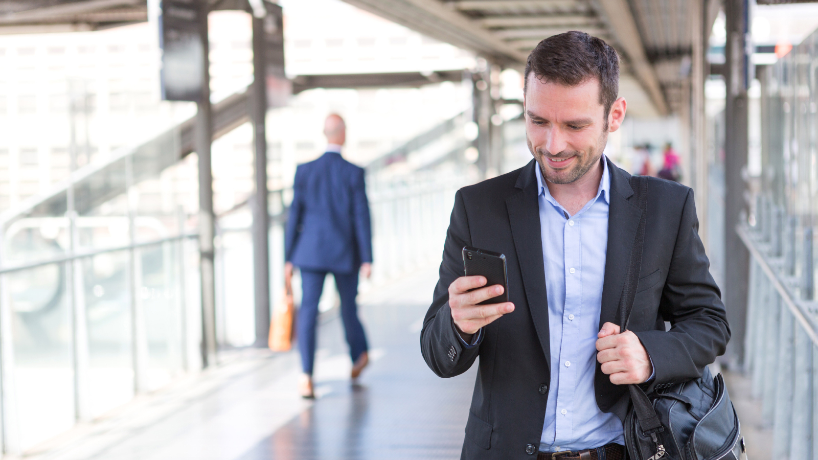 business man walking while looking at mobile phone