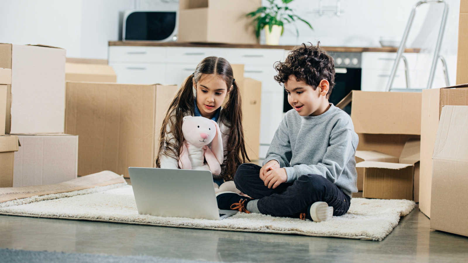 happy children using laptop while sitting on carpet in new home
